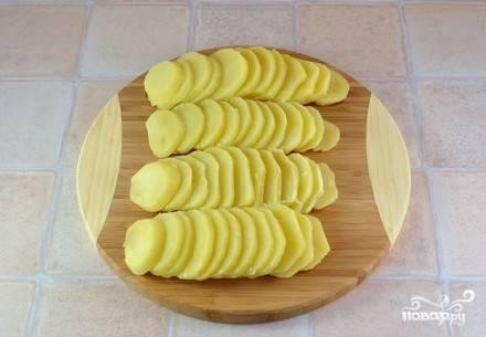 Картофель помойте, очистите и нарежьте пластинками. Очищенный лук мелко нашинкуйте.
