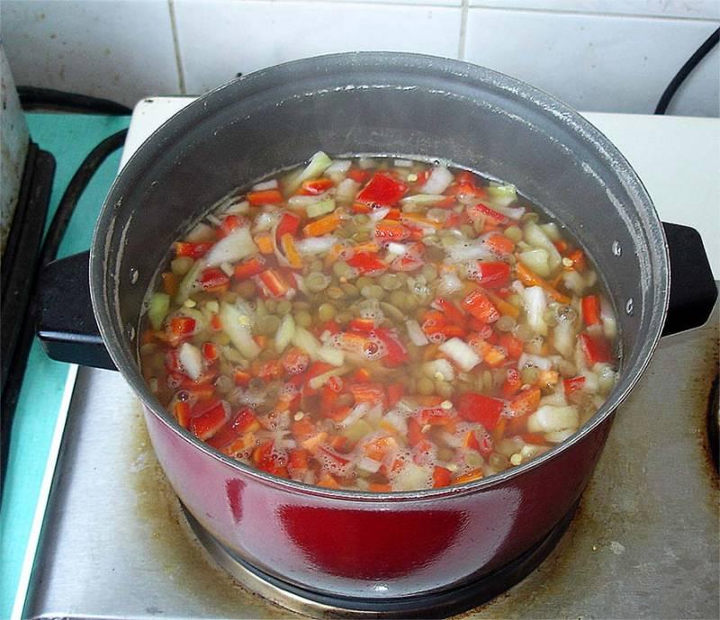 Добавляем в похлебку морковку, лук, перец. Воду можете еще подлить, ведь она выкипает.