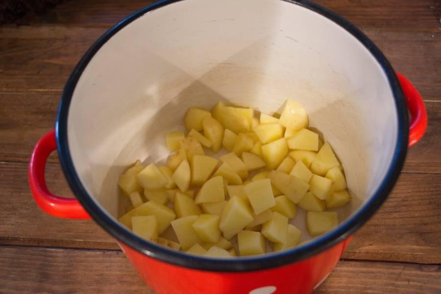 Картофель очистить и нарезать кубиком. Сложите картофель в кастрюлю и залейте кипятком. Поставьте вариться.