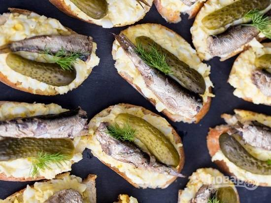 И теперь формируем наши бутерброды. На ломтики батона выкладываем яичную смесь, выкладываем рыбку и ломтик огурца. И украшаем веточкой зелени.