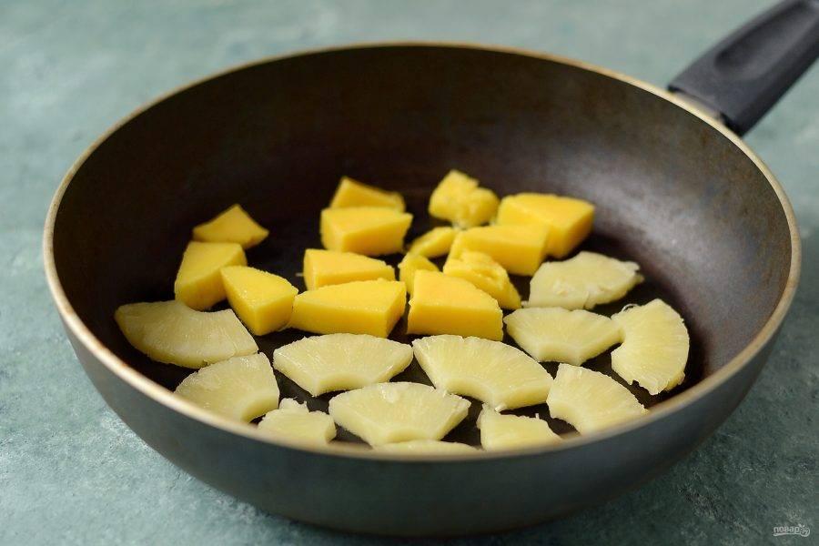 Манго нарежьте квадратиками, колечки ананаса разрежьте на 4 части. Обжарьте фрукты на сухой сковороде до золотистого цвета с двух сторон.