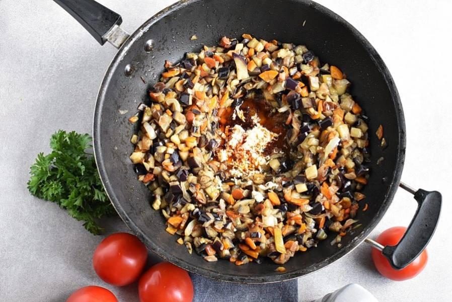 Сделайте углубление в середине жаровни. Выложите туда паприку и крупно растолченный кориандр. Выдавите чеснок. Перемешайте пряности с маслом и прогрейте пару минут, не смешивая с овощами. Затем перемешайте.