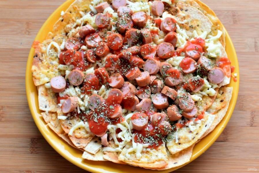 Полейте тортильи томатным соусом для пиццы, щедро посыпьте тертой моцареллой, сверху выложите нарезанные сосиски. И конечно же, не забудьте про оставшийся орегано -  с ним ваша пицца станет еще ароматнее и вкуснее! Поставьте форму с пиццей из начос в духовку минут на 7-10, чтобы сыр как следует расплавился, а краешки чипсов подрумянились.