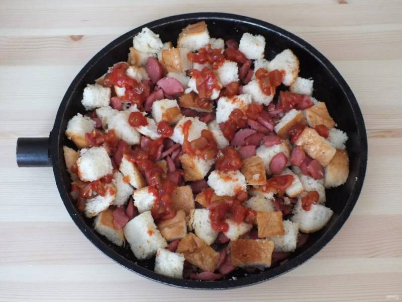Распределите огурцы с томатом по содержимому сковороды.