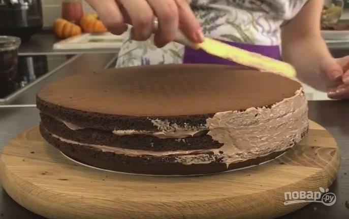 10. Бока торта тоже смажьте кремом, заполните пустоты между коржами. Оставшийся коньячный сироп распределите по всему торту при помощи силиконовой кисточки. После этого торту надо постоять в холодильнике 1-2 часа.