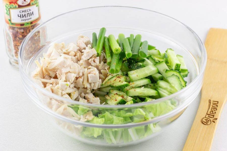 2-3 листа пекинской капусты и огурец нарежьте соломкой, зеленый лук нарежьте крупными брусочками, куриное филе нарежьте кубиками. Выложите всё в салатник и добавьте сухой или свежий перец чили по вкусу.