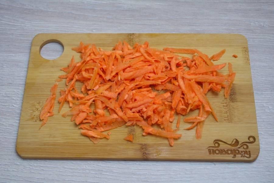 3.  Для измельчения моркови воспользуемся крупной теркой. Морковь натрите на терке с крупными делениями. Добавьте морковь в сковороду к луку, обжарьте все вместе.