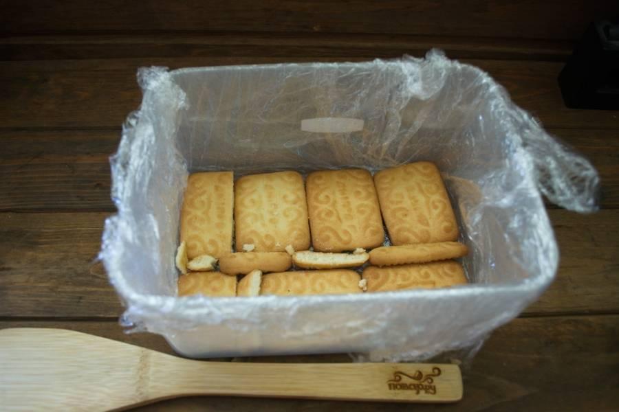Емкость застелите пищевой пленкой. На дно уложите в один ряд печенье. Пустые места закройте кусочками печенья.