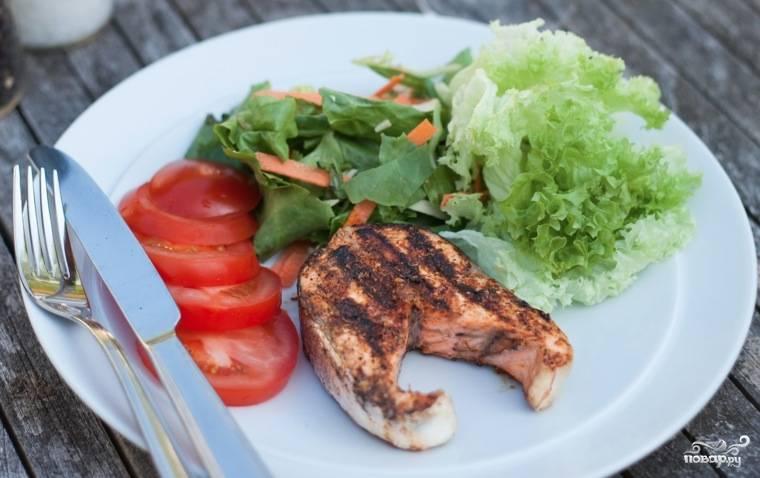 Подавать стейк из лосося следует со свежими овощами.