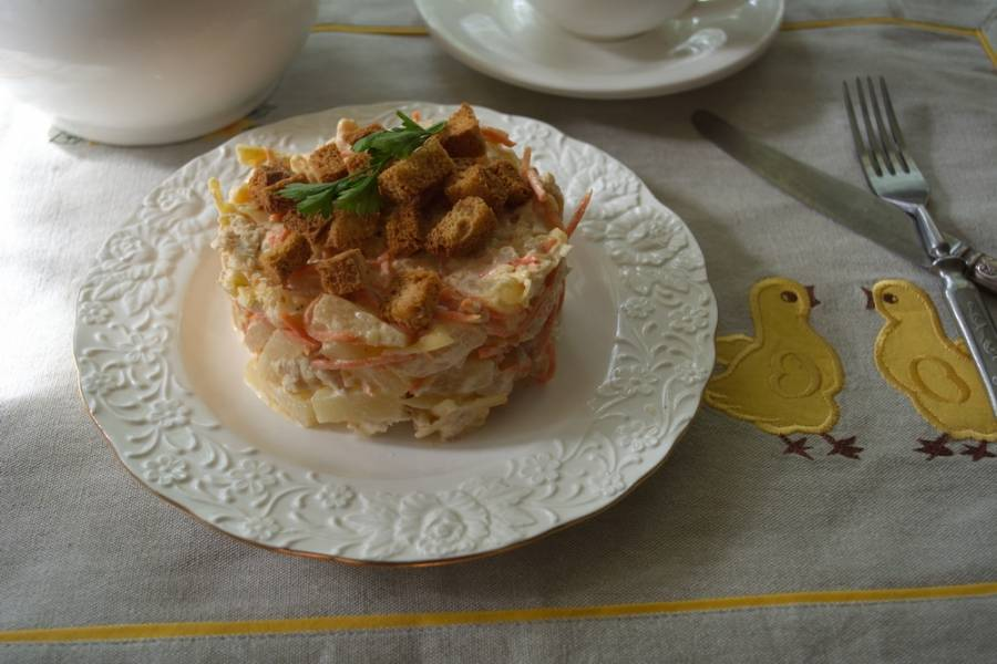 Салат заправьте майонезом и поставьте в холодильник. Пока он там охлаждается, приготовим сухарики. Для этого белый хлеб нужно нарезать на кусочки. Срежьте с каждого корочку, а мякоть нарежьте небольшими кубиками. Подсушите их на сухой сковородке или в духовке. Выложите салат на тарелку. Посыпьте сухариками.