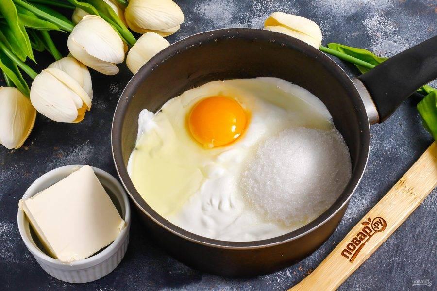 В емкости с антипригарным дном соедините сметану, сахар, лимонный сок. Вбейте туда же куриное яйцо.