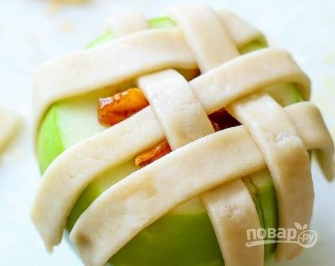 Из яблок вычистите сердцевину. В центр каждого уложите начинку, а сверху распределите 3-4 полоски теста крест на крест. Взболтайте вместе молоко с яйцом. Покройте смесью тесто.