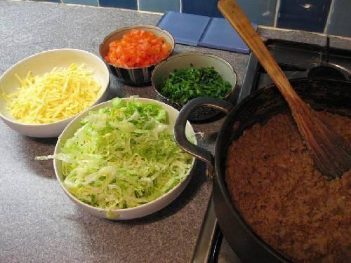 Когда мясо будет готово, нарезаем помидоры, салат и лук.