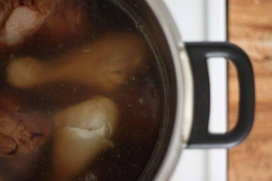 2. Мясо, куриные ножки и ветчину режем крупными кусками и обжариваем на растительном масле, пока не появится корочка. Грибы тем временем замочим в кипятке. Я ножки и вовсе оставляю целыми. Затем заливаем их бульоном, добавим луковицу и морковку для лучшего вкуса. Добавим соус, грибы без жидкости и специи. Доводим до кипения.