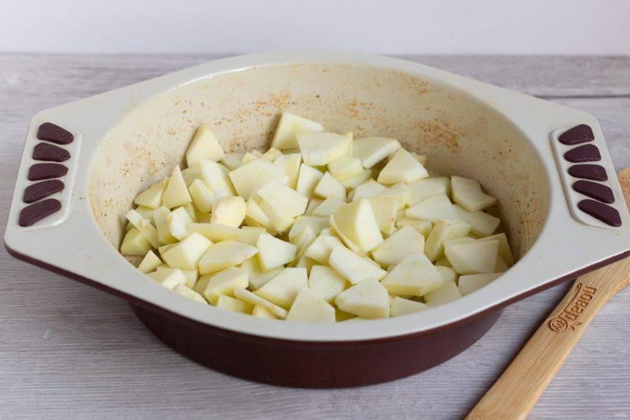 Яблоки помойте, очистите от сердцевины и по желанию от шкурки. Нарежьте небольшими кусочками. Форму (22 см) смажьте растительным маслом и присыпьте панировочными сухарями. На дно формы выложите яблоки.