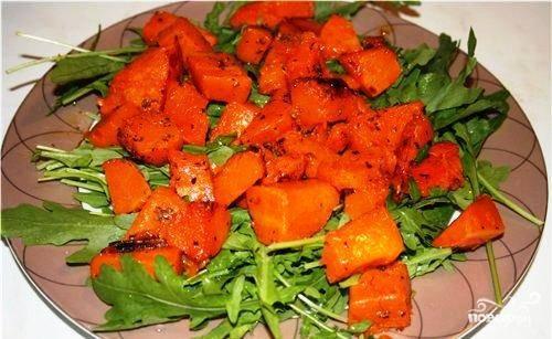 На салатное блюдо выкладываем свежую рукколу, сверху - запеченную тыкву.