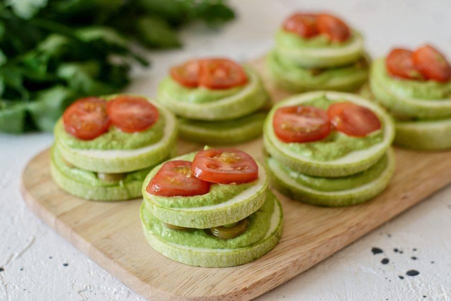 Накройте ещё одним слоем кабачков, а сверху снова зелёный соус и порезанные помидоры черри.