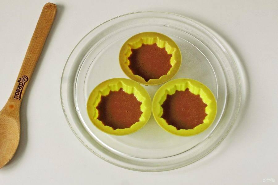 Разлейте тесто по силиконовым формочкам, заполняя их примерно на 2/3. Поставьте формочки в микроволновую печь и готовьте 2 минуты 30 секунд, мощность - 750 Вт. После звукового сигнала дверку не открывайте еще 3 минуты.