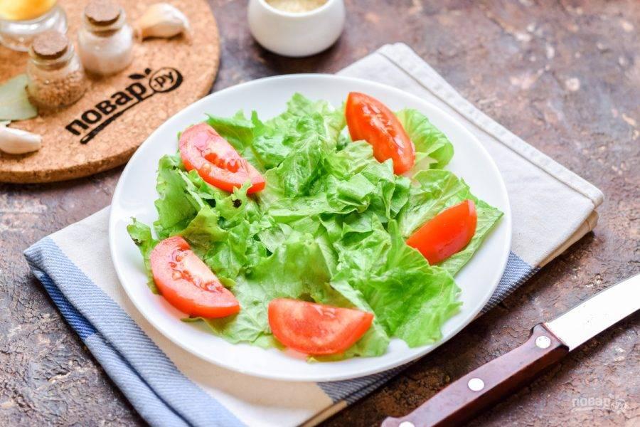 Помидор ополосните, нарежьте небольшими по размеру дольками. Переложите помидорные дольки в салат.