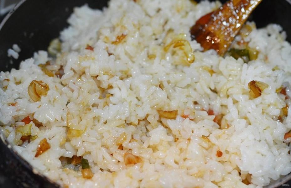 Добавьте вареный рис. И обжарьте всё вместе.