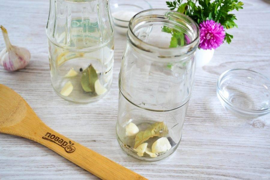 На дно чистых баночек (указанного количества ингредиентов хватит на 2 баночки объемом 450-500 мл.) положите по 1-1,5 нарезанных зубчиков чеснока, по 1 лавровому листику и по 4-5 горошин черного перца.