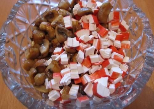 3. А теперь в салатницу складываем рис, грибы с луком, измельченные крабовые палочки, и перемешаем.