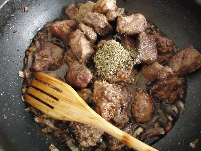Затем верните мясо на сковороду, добавьте вино и специи, перемешайте и тушите на медленном огне 1,5 часа.