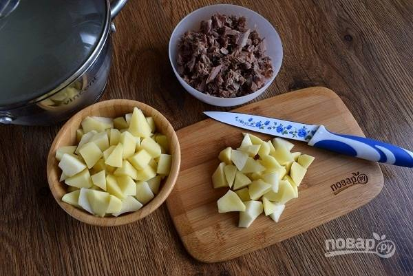 Отварное мясо снимите с кости, порежьте мелкими кусочками, накройте и отставьте пока для подачи. Картофель очистите и порежьте кубиками, закиньте в бульон, варите до готовности.