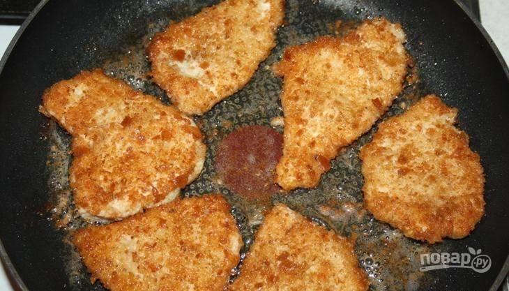 В сковороде разогрейте растительное масло. Выложите в сковороду кусочки курицы в панировке. Обжаривайте до тех пор, пока не появится румяная корочка.