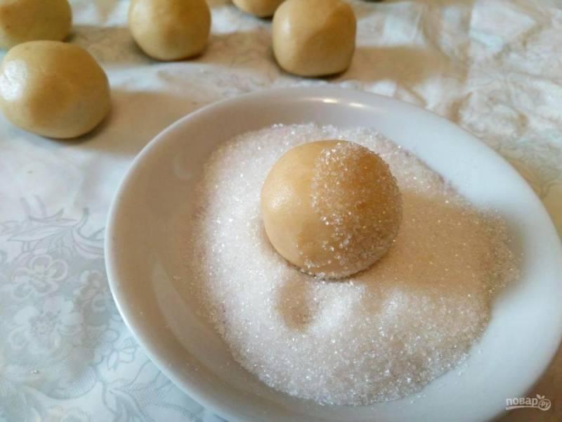 Получившееся тесто разделите на 10-12 частей, каждую из которых скатайте в шарик. Обмакните шарики в сахарный песок.