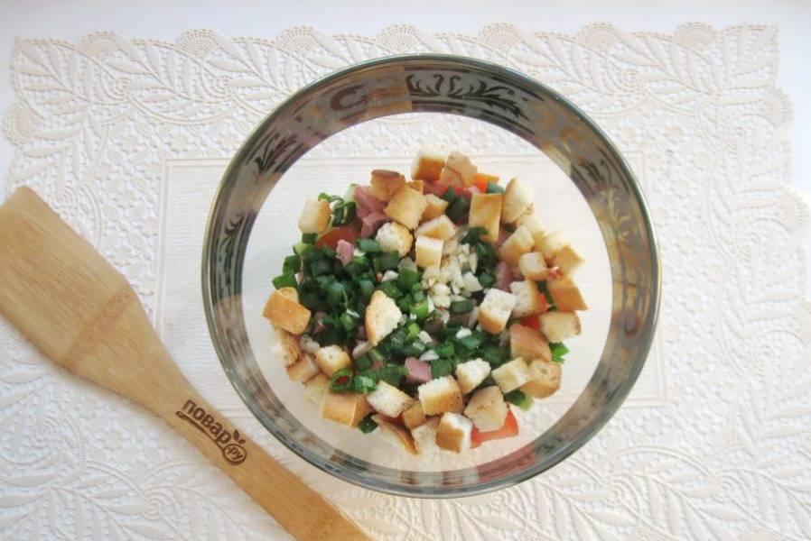 Белую булку нарежьте небольшими кубиками. После поджарьте на сухой сковороде. Выложите сухарики в салат.