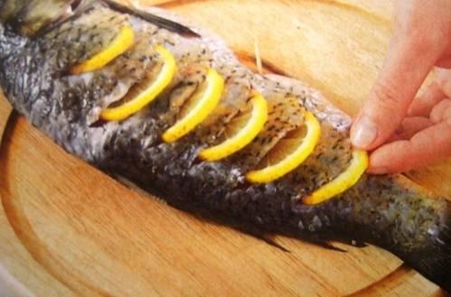 Нарежьте ломтиками лимон. В тушке карпа сделайте надрезы, вставьте туда лимонные дольки. Сбрызгиваем рыбу двумя столовыми ложками оливкового масла и отправляем на гриль на 10 минут.