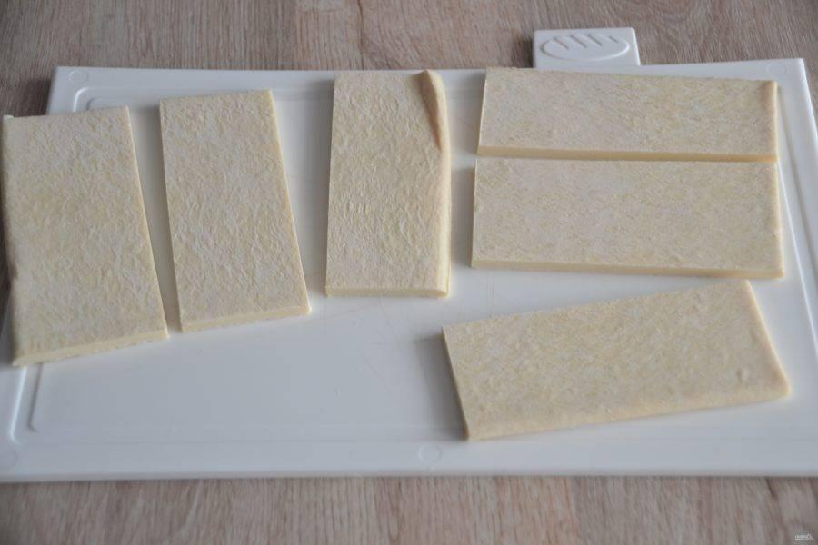 Готовое слоеное дрожжевое тесто предварительно размораживать не надо. При покупке теста не экономьте, выбирайте качественное, с добавлением сливочного масла, а не маргарина. Нарежьте тесто на пластинки, по форме пирожных которые вы собираетесь делать. В данном рецепте использовалась нарезка в форме квадрата и прямоугольника.