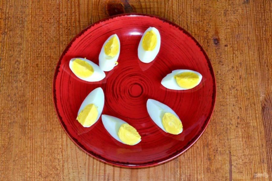 Яйца остудите, очистите и нарежьте на 4 части. Выложите на тарелку для подачи.