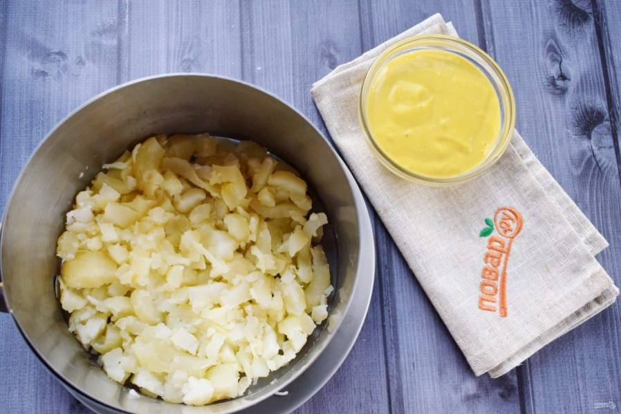 На блюдо поставьте сервировочное кольцо. Салат формируйте слоями. 1-й слой - картофель, натертый на крупной терке. Смажьте майонезом.