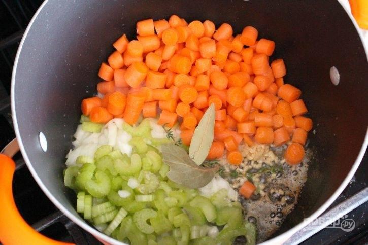 В кастрюле с толстым дном разогрейте масло. Добавьте в него нарезанную средними кусочками морковь, нашинкованный кольцами сельдерей, пропущенный через пресс чеснок и измельчённый лук. Также внесите тимьян, соль, лавровый лист и перец. Готовьте овощи 5 минут, помешивая.