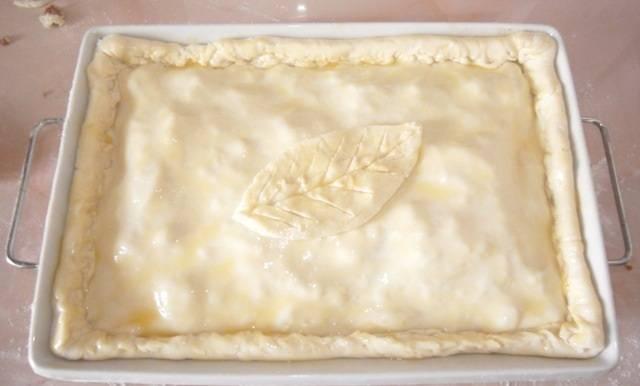 6. Для получения аппетитной корочки сверху пирог можно смазать предварительно взбитым яичным желтком. При желании из остатков теста можно сделать украшения для верхушки пирога. Отправить форму в разогретую духовку.