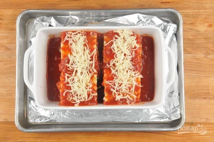 5. В форму для выпечки выложите 2 ложки маринары. Далее рулеты переложите в эту форму. Сверху добавьте оставшийся соус и натрите сыр. Запекайте блюдо в духовке при 200 градусах в течение 30 минут.