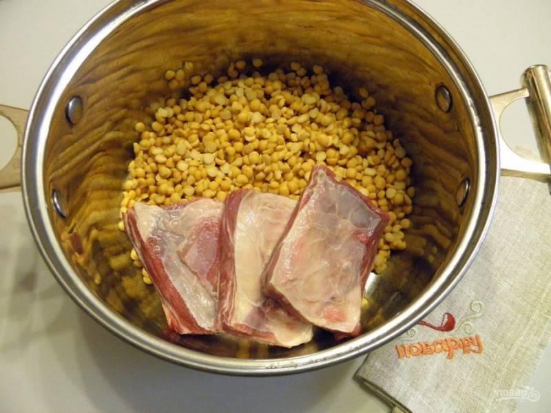 2. Чистый промытый горох сложите в кастрюлю. туда же мясо, посолите и залейте холодной водой. Поставьте на огонь, доведите до кипения и варите 1 час. Пену снимайте, помешивайте.