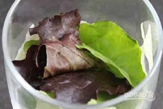 В прозрачные широкие бокалы выкладываем часть листьев салата.