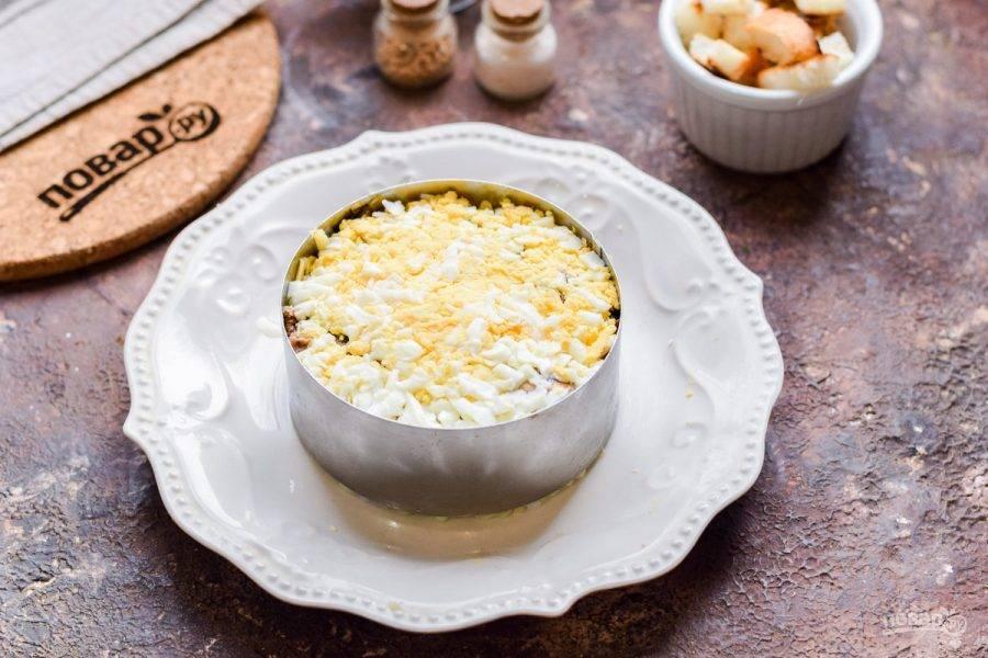 Куриное яйцо почистите и натрите на мелкой терке, выложите в салат.