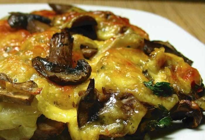 Перекладываем грибы в огнеупорную форму для запекания, хорошенько присыпаем тертым сыром и отправляем в духовку. Запекать 7-8 минут до готовности. Приятного аппетита!
