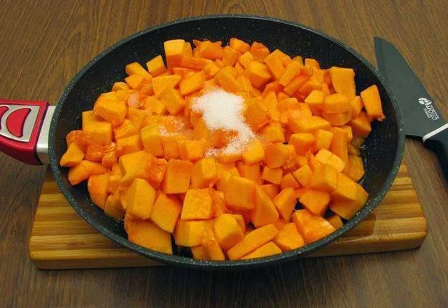 3. На сковороду отправьте сливочное и немного оливкового масла. Разогрейте как следует. Тыкву нарежьте средними кубиками и отправьте на сковороду. Обжарьте на среднем огне. Когда появится румяная корочка, добавьте сахар и аккуратно перемешайте.