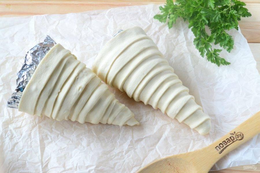 Размороженное слоеное тесто порежьте на полоски шириной 2 см. Этими полосками обмотайте подготовленные формы, начиная от самой узкой точки.