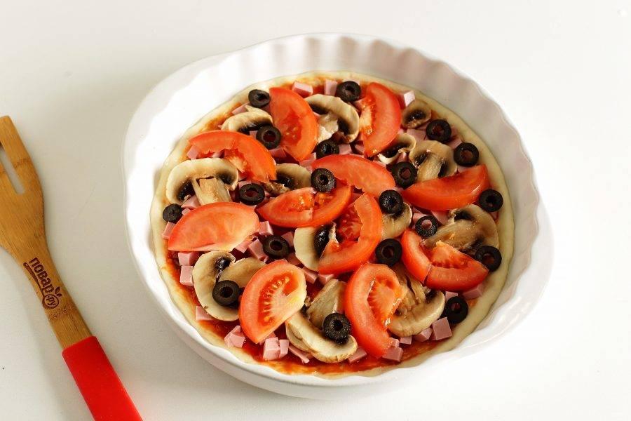 Сверху распределите начинку. У меня нарезанная кубиками колбаса, помидоры дольками, маслины и нарезанные шампиньоны.