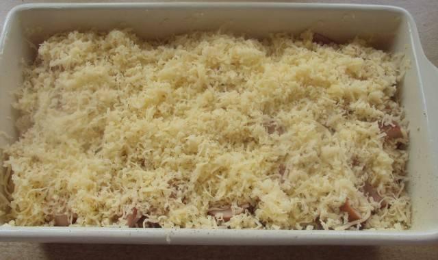 Заливаем полученной смесью макароны с сосисками и посыпаем сверху натертым сыром.