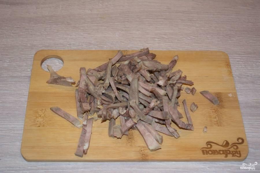 Отварной язык нарезаем небольшой соломкой. Для приготовления салата подойдет и свиной, и говяжий язык. Все зависит от того, какой проще вам купить.