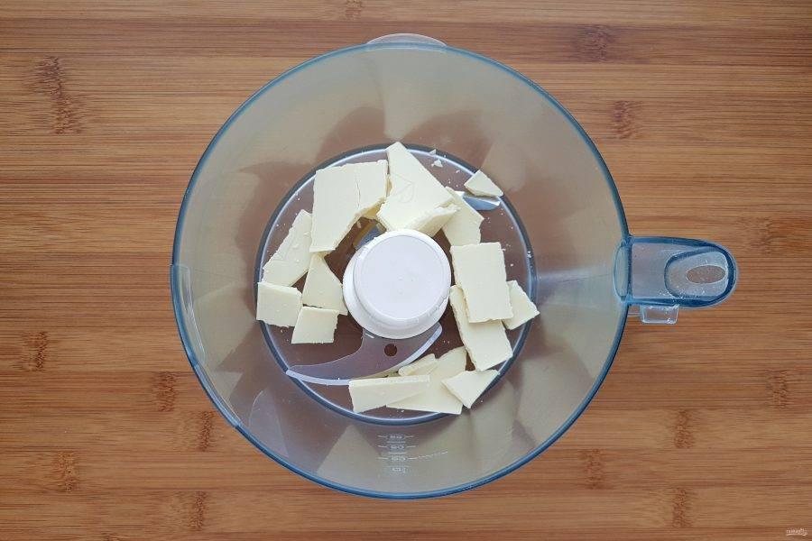 Измельчите белый шоколад. Очень удобно и быстро это делать при помощи комбайна с острым ножом.