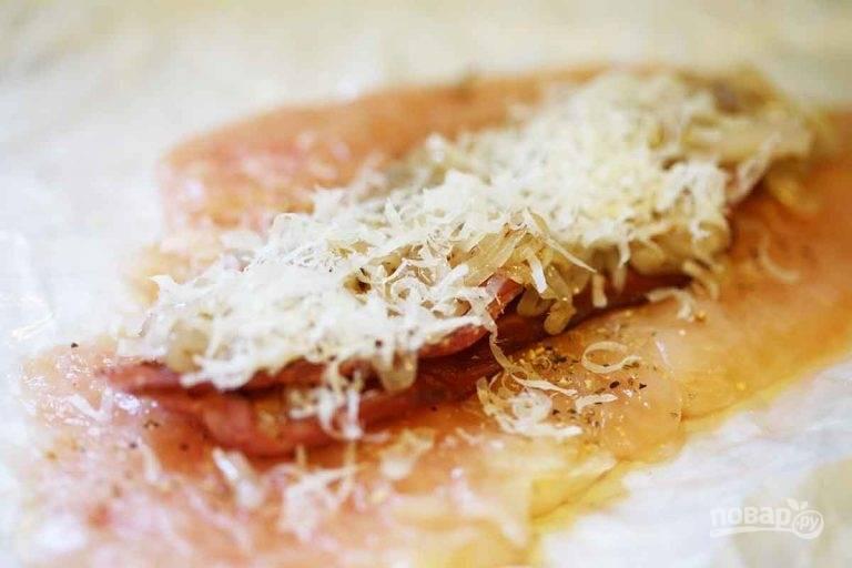 2.Выложите куриную грудку, посолите и поперчите. Выложите на каждую грудку по 2-3 ломтика бекона, затем посыпьте обжаренным луком и добавьте тертый сыр.