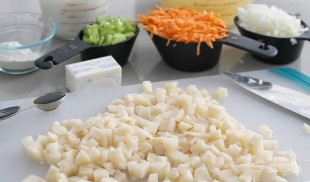 1.Вымойте и очистите овощи: нарежьте мелкими кубиками картофель, измельчите сельдерей, лук, натрите на крупной терке морковь, нарежьте мелко чеснок.